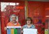 La bibliotecaria grausina, Pepa Mur, y un colaborador posan con los carles concienciadores del Día de la Dislexia (Foto: Angel Gayúbar)