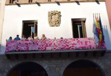 Voluntarias de la AECC engalanado del rosa reivindicativo el balcón de la casa consistorial de Graus (Foto: Angel Gayúbar)